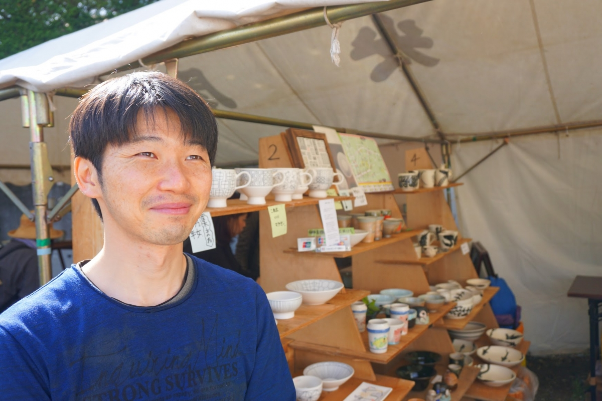 Katsumura in front of his booth, which he shared with another ceramic artist.